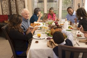 Family sitting at a dinner table - picture to illustrate how to represent yourself in family court